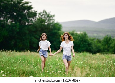 Little girl with a beautiful mom walks in the park on the nature in the mountains