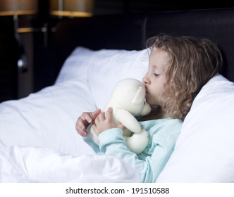 the little girl in bed with a toy