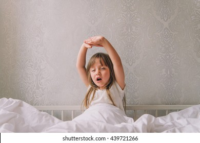 Little girl in the bedroom is sitting on the bed. Little girl is wearing a pajamas and sitting in bed stretching and yawns.