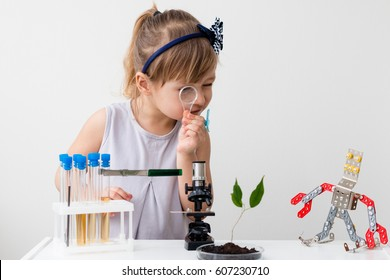 Little girl is behind the desk. Microscope and the tree are near her. Little robot. E-learning. Stem education.