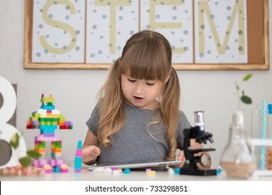 Little girl is behind the desk. Microscope, the tree, little robot and books are near her. The word STEM is on the background. E-learning. Stem education. Cute child.
