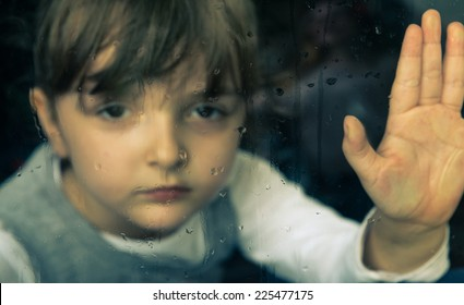little girl behind window. rain drops on the glass. the girl wants to go playing outside but it s not possible because of the bad weather