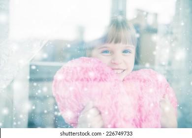 Little girl behind a window. It's snowing outside.
