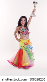 Little girl bellydancer in colorful costume with goblet of the winner portrait