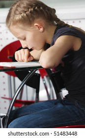 Little girl bending over book at cafe table