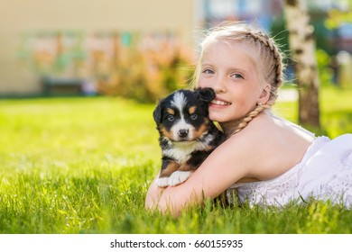 Little girl with a berner sennenhund puppy, outdoor, summer