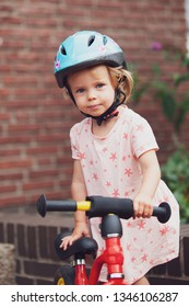 little girl with bicycle and  helmet smiling