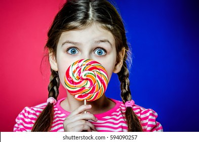 Little girl with big beautiful green eyes holding a big colorful caramel candy.