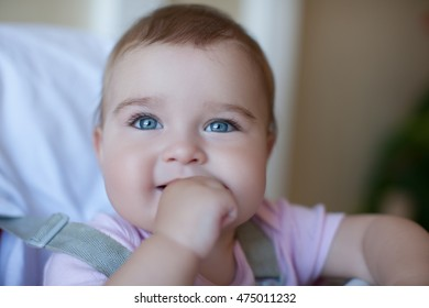 Little Girl with big Blue Eyes gnaws her finger and scratches the gum, the first teeth. Beautiful Little Girl HAND IN MOUTH