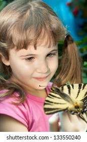 little girl with a big bright butterfly on her hand