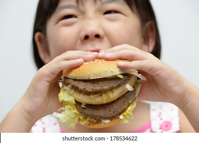 Little girl with big burger or sandwich inside mouth