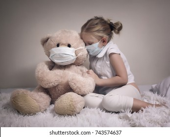 Little girl and big plush bear in medical masks. The concept of childhood diseases, empathy, support and help sick children