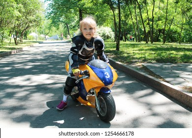 Little girl biker in motorcycle protection on a children's electric motorcycle rides a bike through the park at a biker festival motorcycle on an electric motor without emitting green technologies in