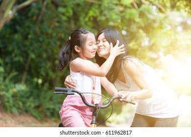Little girl biking in the park, mother giving a goodbye kiss , Asian family outdoor fun activity.