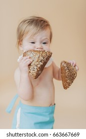 the little girl bites a roll, a bakery product in the child's hands