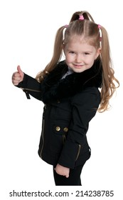 A little girl in the black coat holds her thumb up