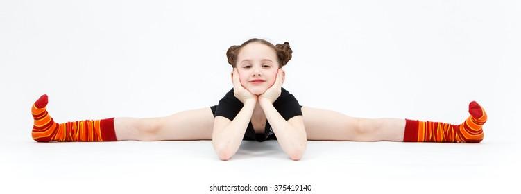 Little girl in black dress doing gymnastic split on white background