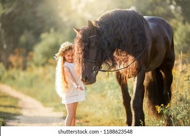 Little  girl with black friesian stallion at summer evening