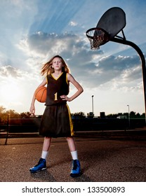 Little girl in black and gold basketball uniform standing next to playground hoop with ball, dramatic sky