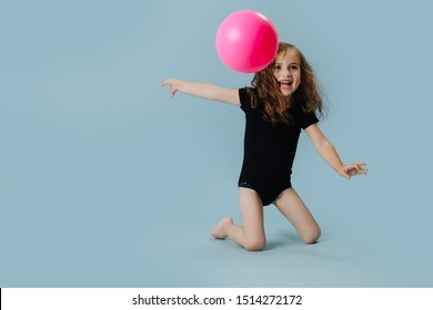 Little girl in a black leotard with pink gymnastic ball over blue background. She is doing element with a ball.