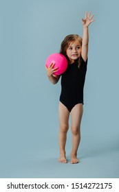 Little girl in a black leotard with pink gymnastic ball over blue background. She is doing gymnastic forms and stances.