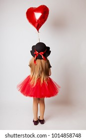 little girl in a black red dress and black hat with a red balloon on a white background back view
