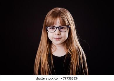 little girl blond in glasses smiles in black jacket on a black background