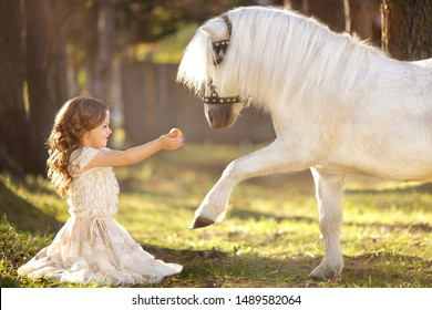 little girl with blond hair in a beautiful dress walks through the woods with a white pony and feeds him apples