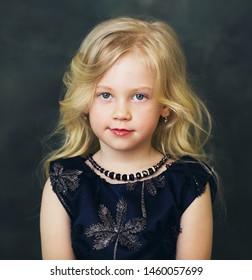 little girl with blond hair over dark background