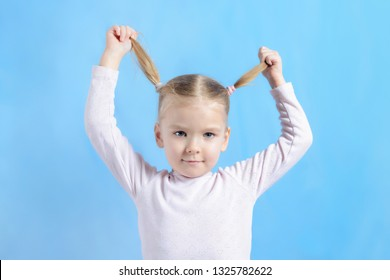 A little girl with blond hair pulls her tails in different directions. Cute baby dabbles and have fun. Bright photo on blue background.