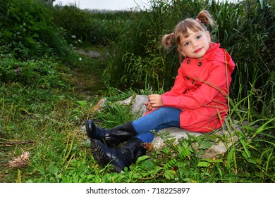 little girl with blond hair in a red raincoat near a lake with toy