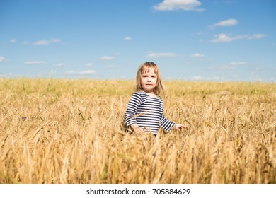 Little girl with blond hair in a striped shirt stands in a field
