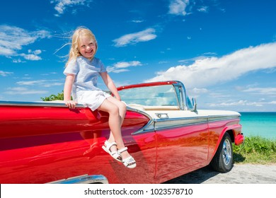 Little girl with blond hair, sunglasses and blue blouse is seating on red retro car cabriolet on the coastline of Caribbean sea