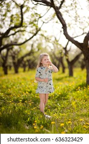 A little girl with blond hair walks in the garden and sniffs flowers, emotions, joy