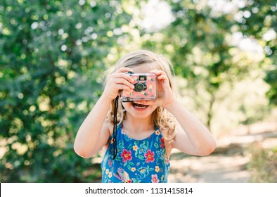 A little girl with blonde curly hair take a picture with a disposable camera decorated with pineapples - summer fun