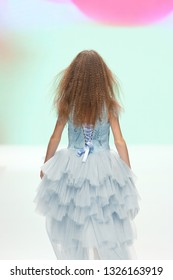 Little girl with blonde hair in blue tulle dress, back view
