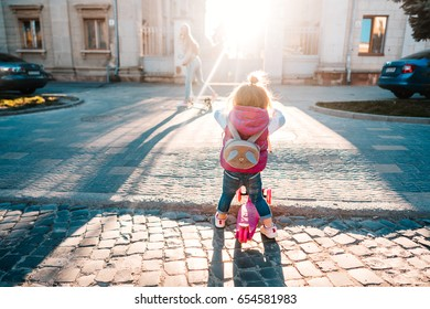 Little girl with blonde hair rides on scooter on street.