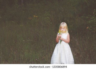Little girl with blonde hair in a white dress stopping to smell the flowers