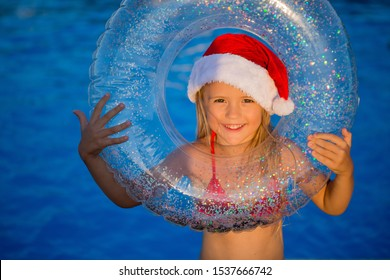 little girl blonde in a Santa hat and swimming around in the pool in the summer, the concept of celebrating Christmas and new year in tropical countries