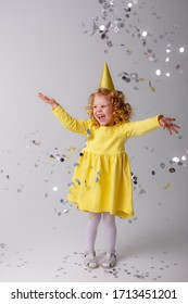 little girl blonde in a yellow dress catches confeti smiling happy on white background
