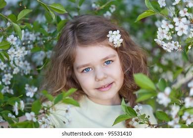Little girl in the blossom cherry garden in spring season