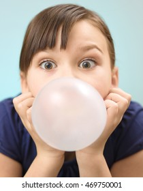 Little girl is blowing big bubble gum, closeup portrait