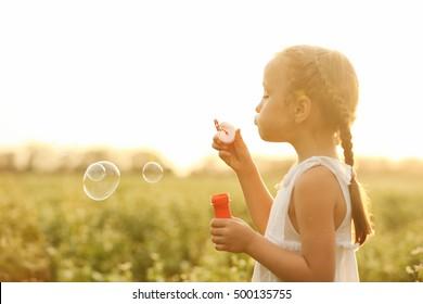 Little girl blowing bubbles in field
