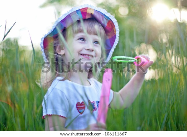 Little girl blowing bubbles in the green grass