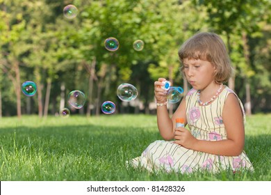 A little girl is blowing bubbles sitting on the green grass in the park