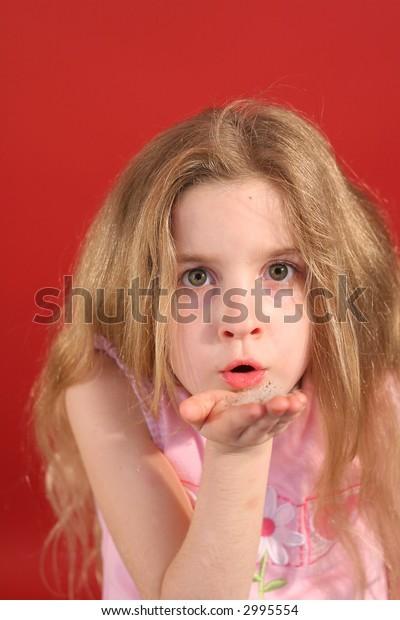 little girl blowing flowers