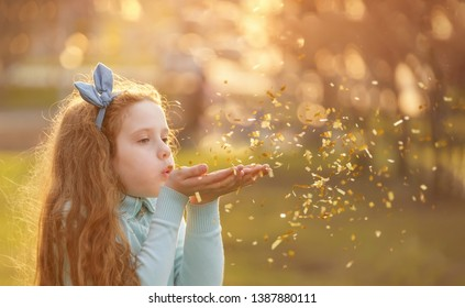 Little girl blowing gold confetti with her hand. Holiday, happy childhood, healthy lifestyle concept.
