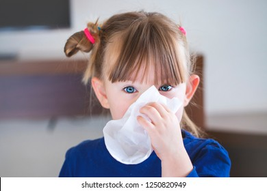 little girl blowing her nose into a handkerchief.