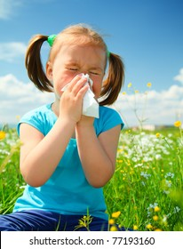 Little girl is blowing her nose while sitting on green meadow
