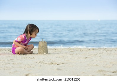 Little girl blowing on cake made with sand. Photo taken near the ocean.